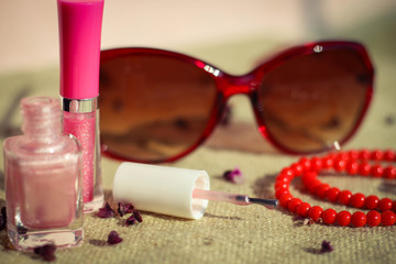 Women's accessories: sunglasses, lip gloss, nail polish, beads