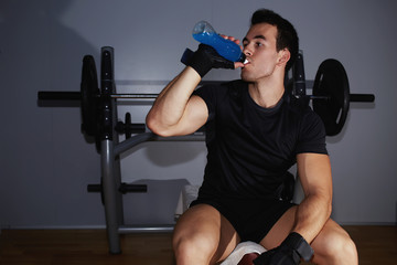 Athletic man refreshing with energy drink after hard training