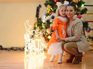 moter and daughter near the christmas tree