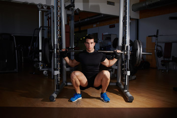 Professional bodybuilder doing squats with barbell at gym
