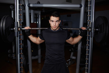 Half length portrait of athletic man doing squats working out