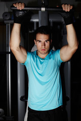 Young athletic man with muscular body doing pull up exercise