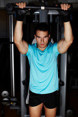 Portrait of attractive man doing exercise on pulls ups machinea
