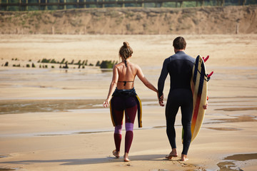Rear view of young couple walk at the beach with surfboard holdi
