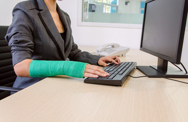 Injured businesswoman hand  typing on computer keyboard.