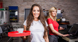 Fototapety Smiling waitress serving hot coffee in the coffee shop