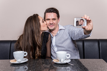 Loving couple taking selfie at cafe