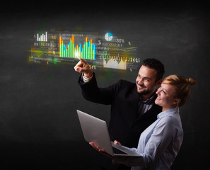 Young business couple touching colorful charts and diagrams
