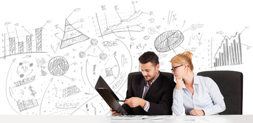 Business persons at desk with hand drawn charts