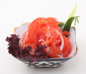 The cut tomatoes with onions and salad leaves