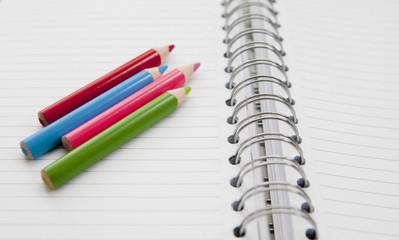 crayons de couleurs sur carnet de notes