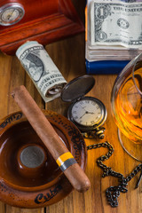 Wealthy man desk, cuban cigars dollar notes, vintage watch and a