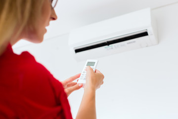 Woman using air-condition with remote control