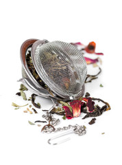 Green herbal tea with dried flowers in tea strainer