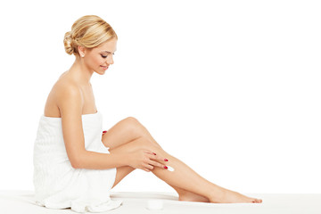 Young woman applying body cream on legs