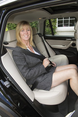 Woman in car wearing business suit adjusting seat belt