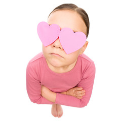 Little girl is holding hearts over her eyes