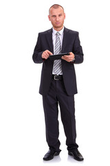 Businessman in a dark suit, holding a tablet,  consulting the la