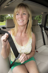 Female passenger in a rear seat of a car adjusts seatbelt