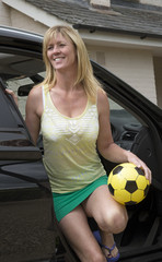 Woman getting out of a car holding a football