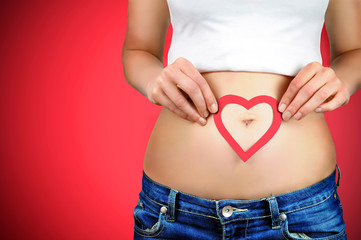 Red heart shape on a woman´s stomach.