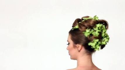 Beautiful woman with orchid flower in hair posing
