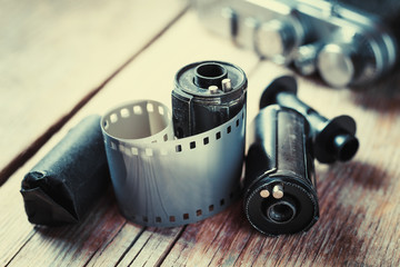Old photo film rolls, cassette and retro camera on background. V