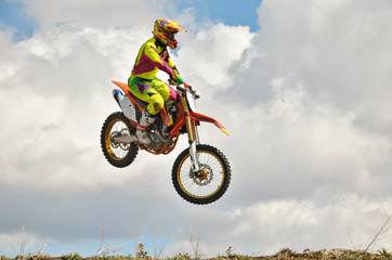 Motocross rider on a motorcycle spectacularly lands on a edge of