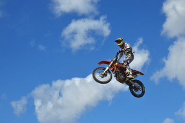 MX rider on the motorbike takes off from the hill