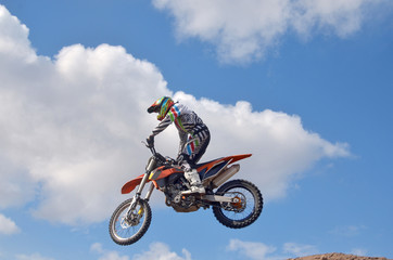 Exstrim driver standing on the MX motorcycle is flying over the