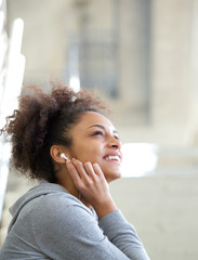 Happy young woman listening to music with earphones