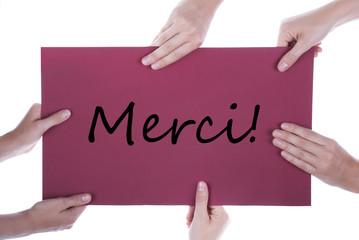Viele Hände halten ein Plakat mit dem französischen Wort Merci