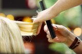Fototapety Hairdresser trimming blond hair with scissors