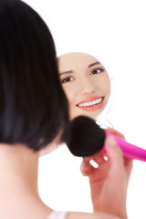Happy woman doing make up using a mirror