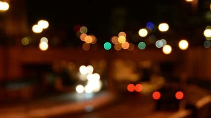 Cars passing under a bridge at night and fading out of focus