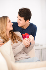 young couple man woman at home offering gifts for lover's day