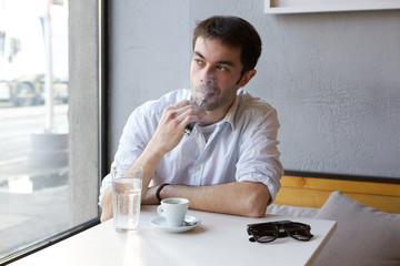 Young man smoking vapor cigarette indoors