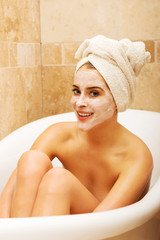 Woman sitting in bath with face mask