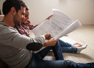 Young couple examing blueprints of they new house.