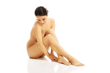 Slim nude woman sitting on the floor