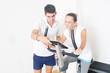 canvas print picture - Coach zeigt Frau Fitnessfahrrad