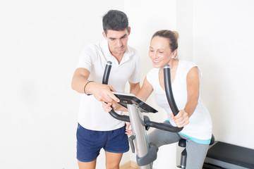 Coach zeigt Frau Fitnessfahrrad