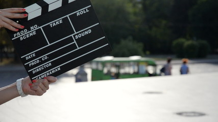 female hands holding a clapper board