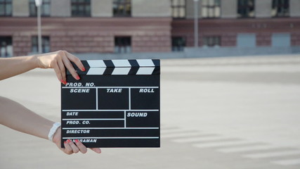 female hands holding a clapper board. close-up