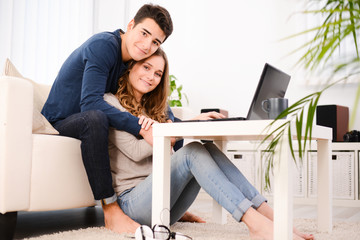 happy young couple together at home playing on internet