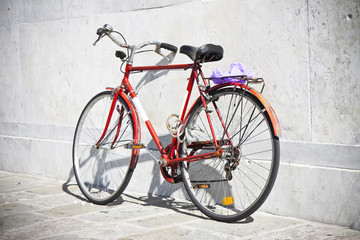 Red bicycle against a marble wall