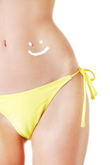 Sunscreen lotion over female slim belly