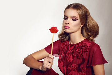 Beautiful sexy woman in silk dress with candy lips on stick