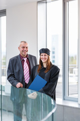 Pretty female university graduate with her happy and proud fathe