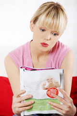 Pretty blonde woman reading a newspaper